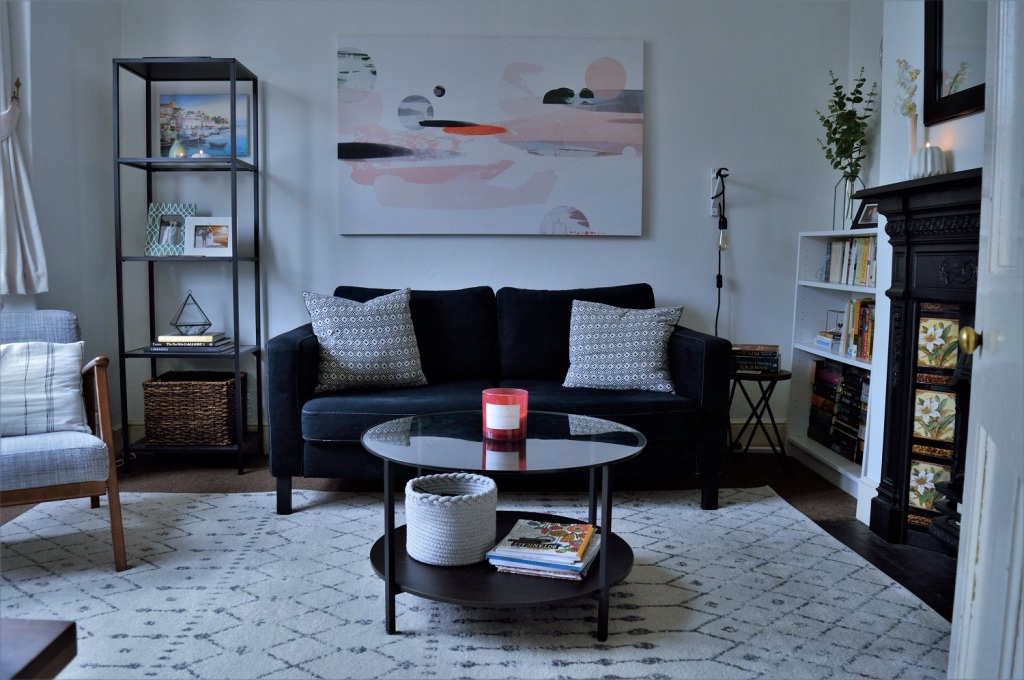 Living room with black sofa and white rug